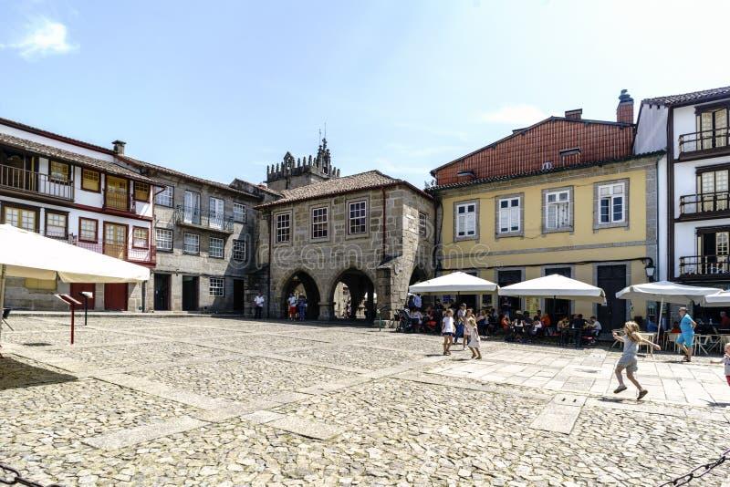 Guimaraes, Portugal 14 augustus, 2017: Het vierkant van de binnenstad van het dorp met van de keivloer en steen voorgevels van ou stock foto's
