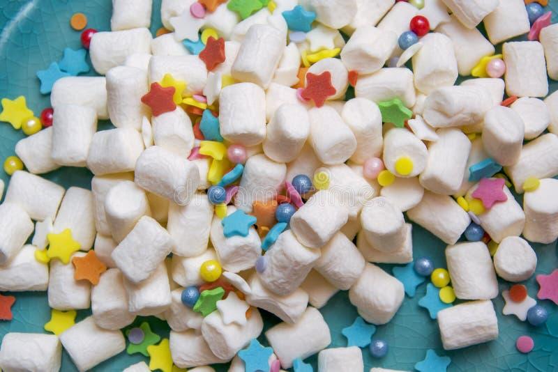 Guimauve et arrosage de fête coloré d'un plat bleu Macro image libre de droits
