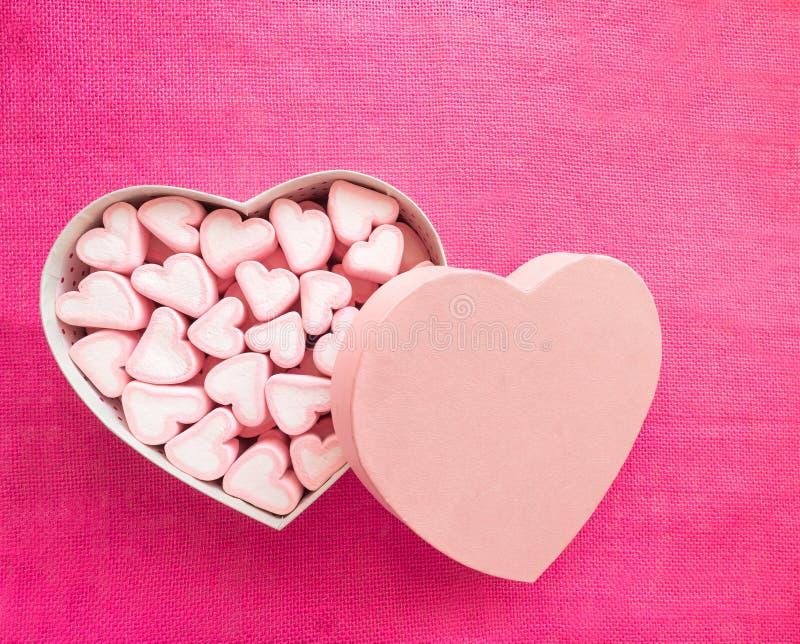 Guimauve rose dans un boîte-cadeau sous la forme de coeur sur le fond de textile, beaucoup de guimauves de coeurs pour le présent photo stock