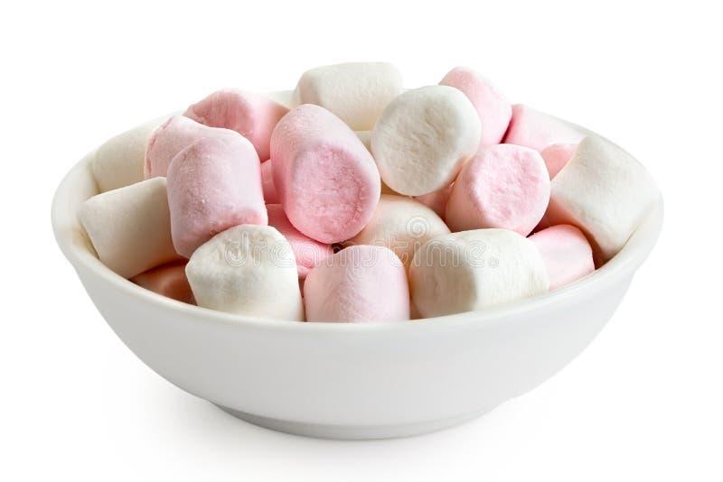 Guimauves de rose et blanches mini dans le plat en céramique blanc d'isolement sur le blanc photographie stock