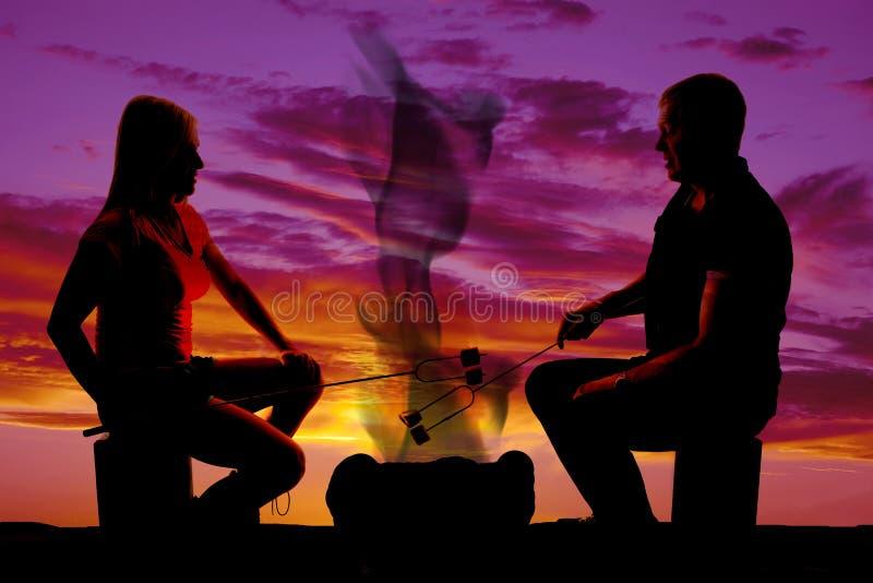 Guimauves de torréfaction d'homme et de femme de silhouette photo libre de droits