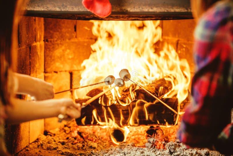 Guimauves de torréfaction de famille par le feu Maison confortable de chalet avec photos stock
