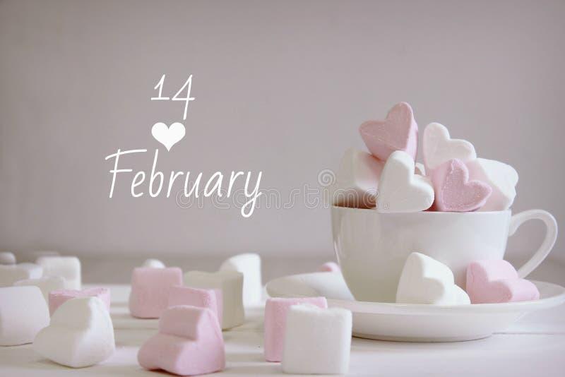 Guimauves douces sous forme de coeur dans la tasse en céramique avec le fond rose Concept au sujet de l'amour et des relations St photographie stock libre de droits