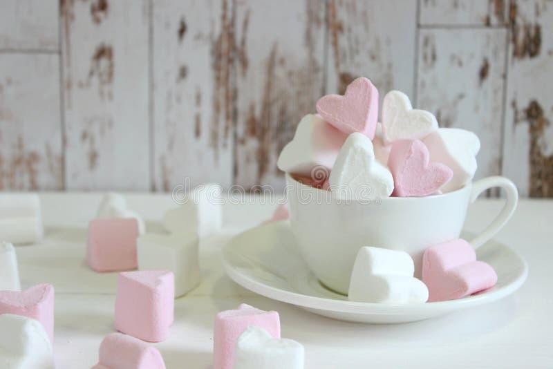 Guimauves douces sous forme de coeur dans la tasse en céramique avec le fond rose Concept au sujet de l'amour et des relations St photographie stock