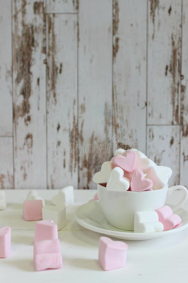 Guimauves douces sous forme de coeur dans la tasse en céramique avec le fond rose Concept au sujet de l'amour et des relations St photos stock