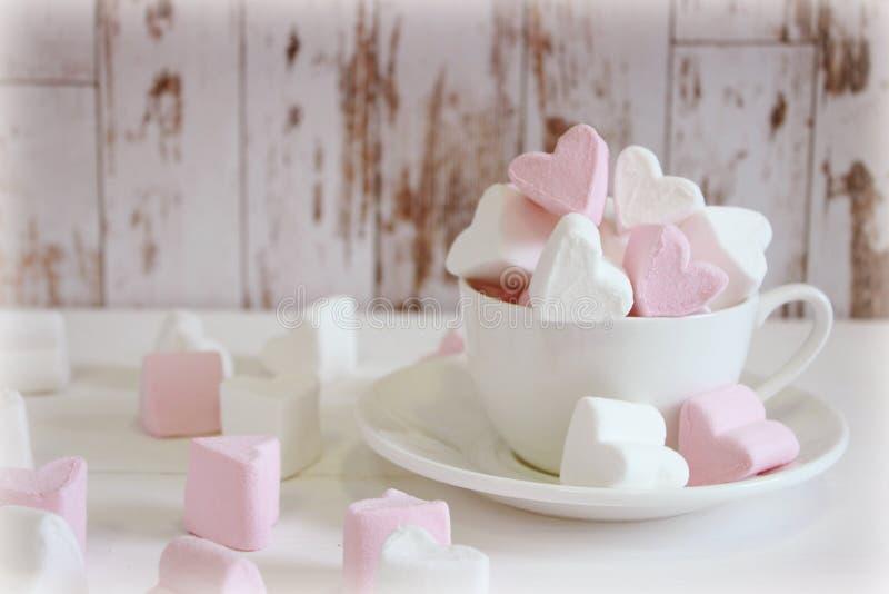 Guimauves douces sous forme de coeur dans la tasse en céramique avec le fond rose Concept au sujet de l'amour et des relations St image libre de droits