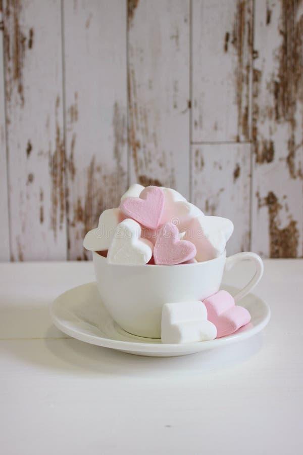 Guimauves douces sous forme de coeur dans la tasse en céramique avec le fond rose Concept au sujet de l'amour et des relations St photo stock