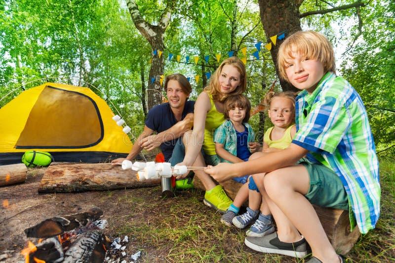 Guimauves heureuses de torréfaction de famille dans les bois image stock