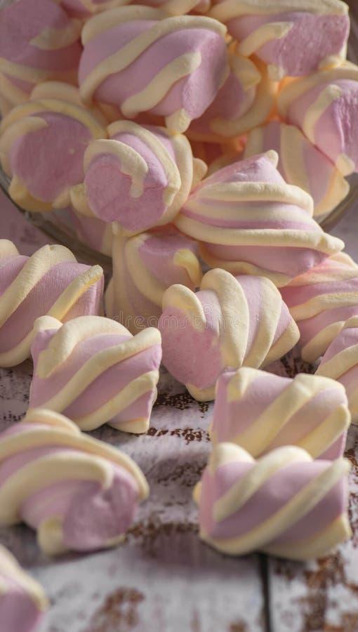 Guimauves roses avec les boucles blanches obtenant assez de sommeil avec un conteneur transparent sur le fond en bois clair image stock
