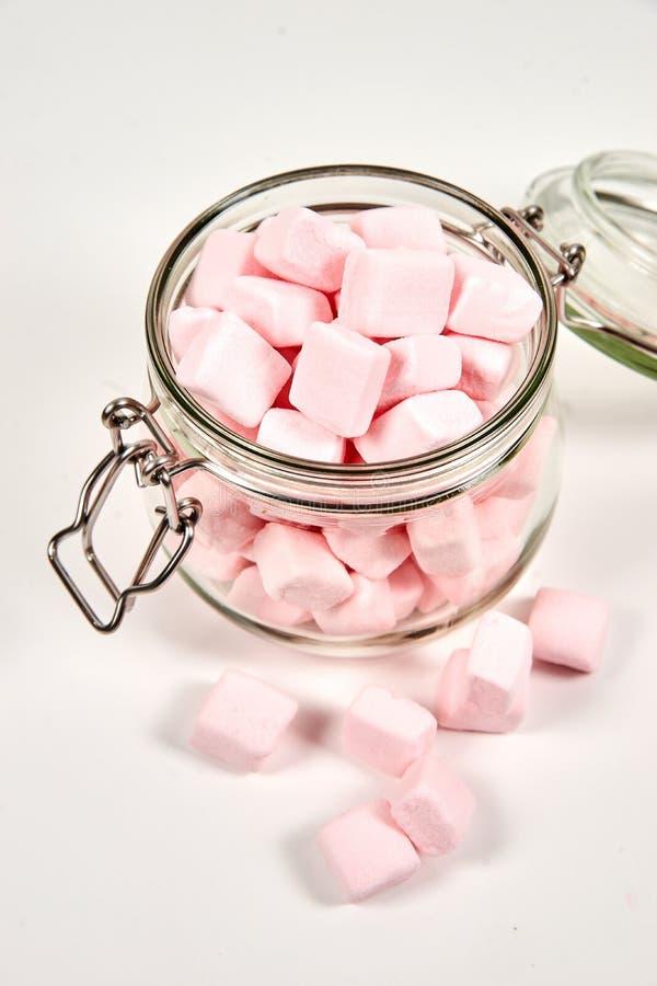 Guimauves roses dans le pot en verre, sur le fond blanc photographie stock libre de droits