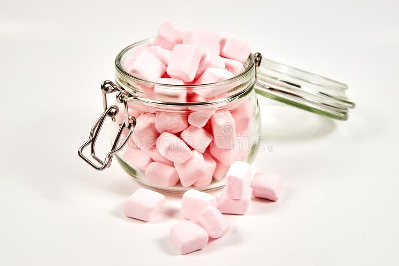 Guimauves roses dans le pot en verre, sur le fond blanc image libre de droits