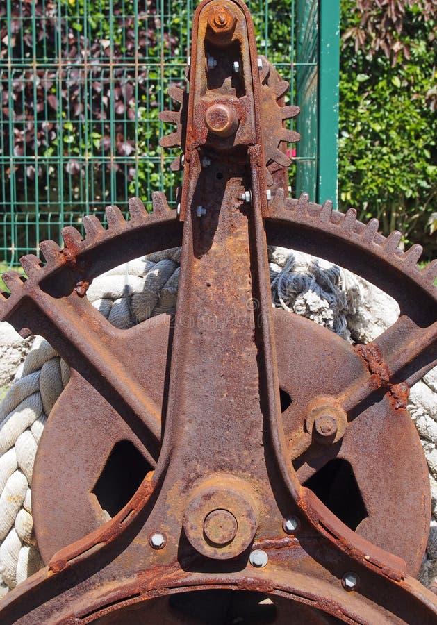 Guincho oxidado em desuso velho do ferro com as engrenagens e corda quebradas da roda da roda denteada imagens de stock