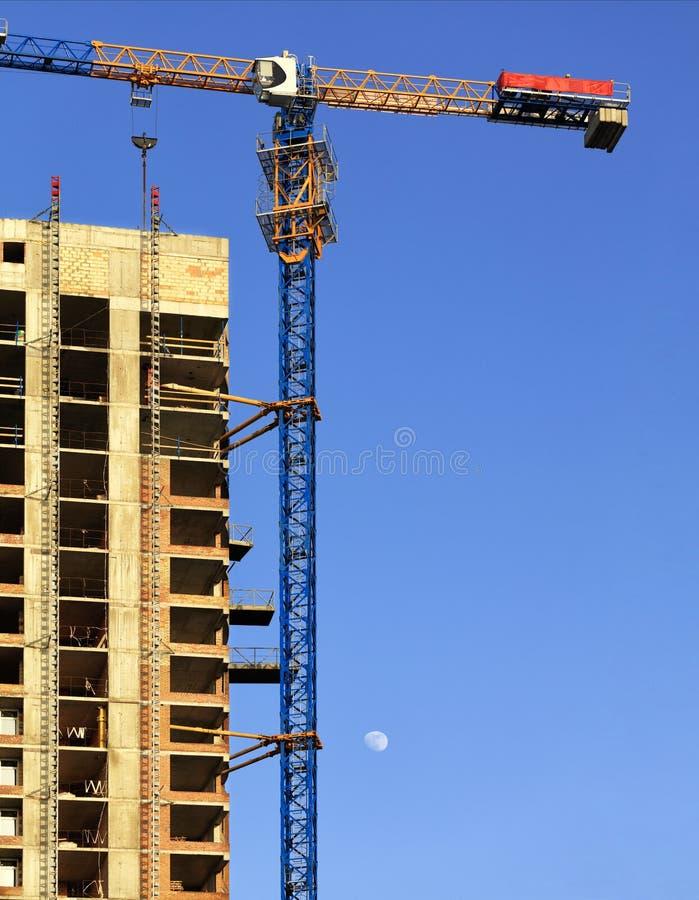Guindaste da fachada e de construção perto da construção concreta moderna sob a construção foto de stock