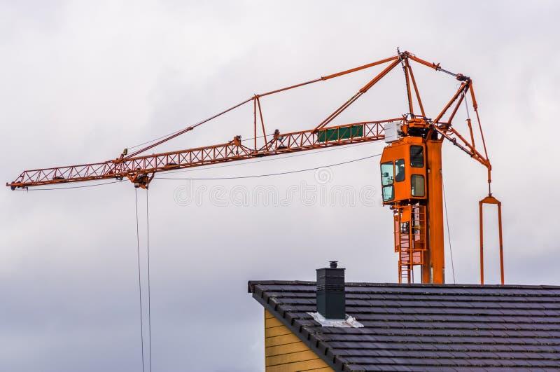 Guindaste de construção com um céu nebuloso no fundo, equipamento da indústria da construção civil, maquinaria pesada fotos de stock royalty free