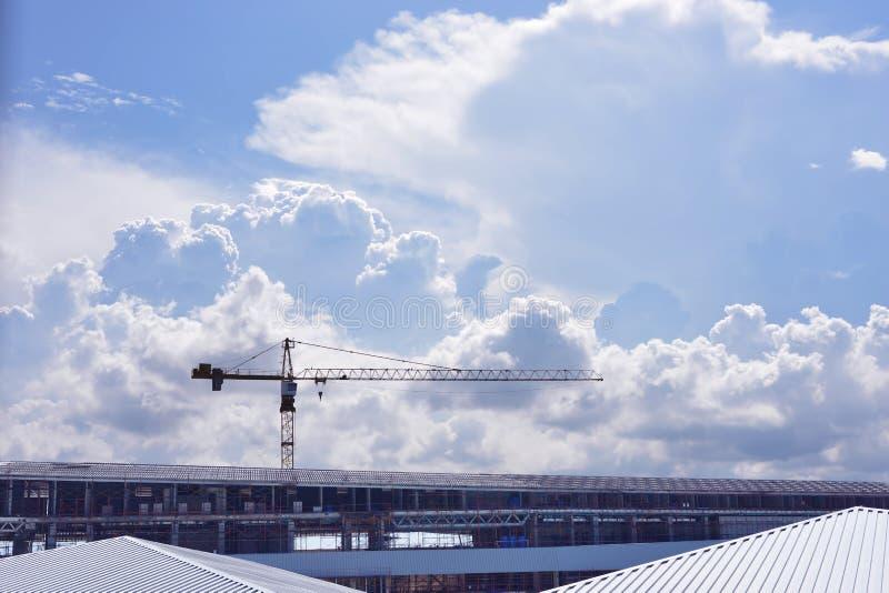 Guindaste de construção sobre uma construção com a nuvem no céu imagem de stock