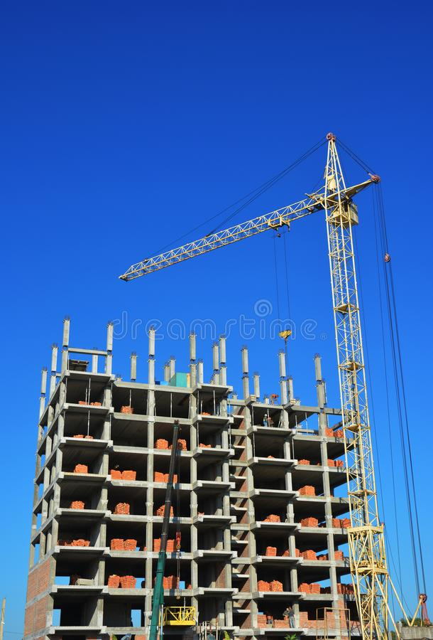 Guindaste de torre com o local industrial da construção civil com os contratantes na parte superior foto de stock royalty free