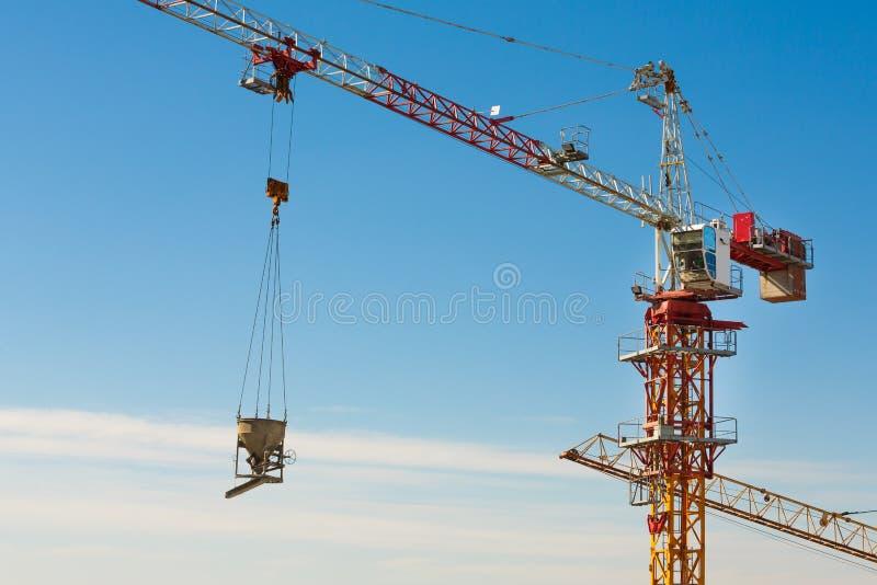 Guindaste de torre que levanta acima de uma cubeta do cimento na área da construção fotografia de stock royalty free