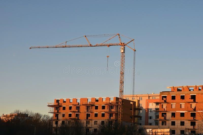 Guindaste e construção de construções novas Fundo bonito para a indústria da construção civil no por do sol fotografia de stock