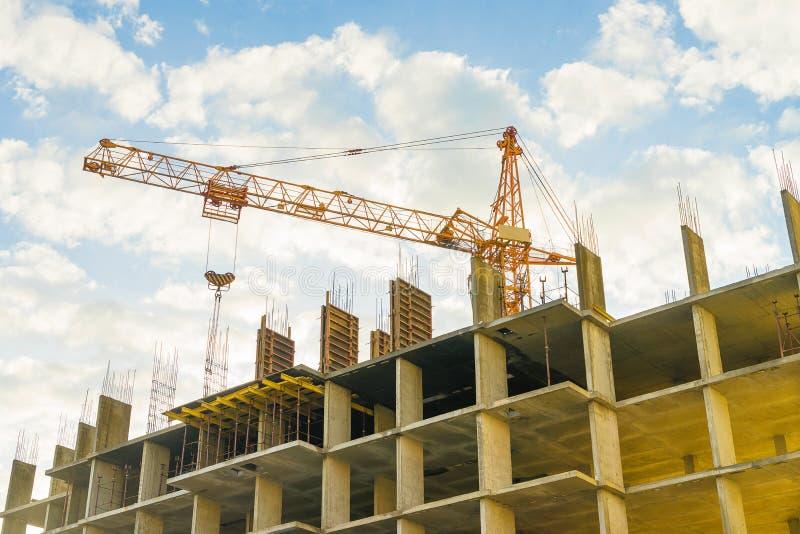 Guindaste e construção sob a construção contra um céu nebuloso foto de stock royalty free