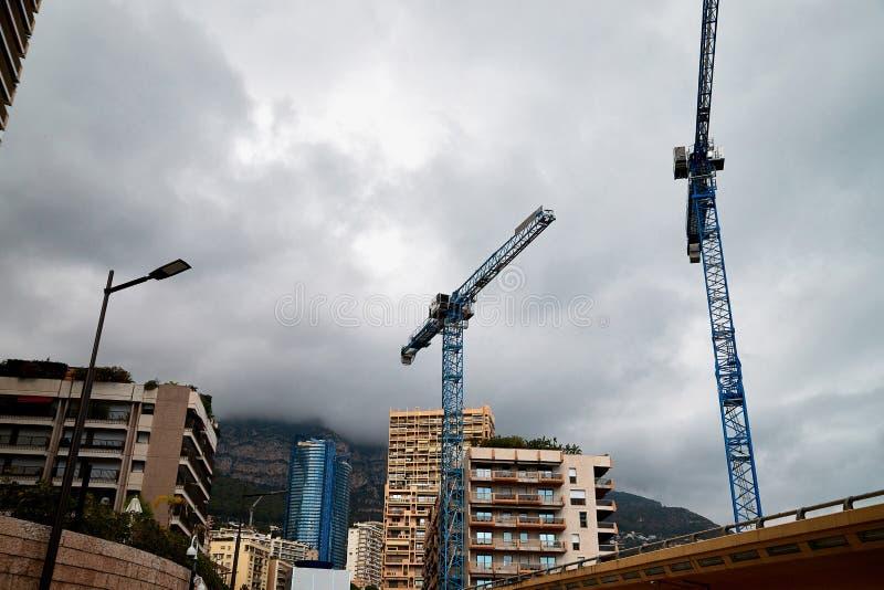 Guindaste e constru??o de torre contra a montanha e o c?u foto de stock