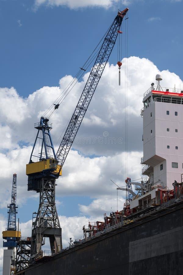 Guindaste e torre de controlo do porto da carga contra o céu azul com clo fotos de stock royalty free