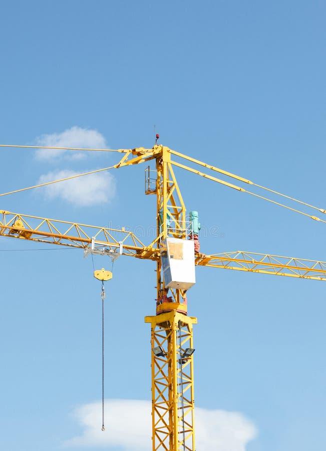 Guindaste industrial amarelo e céu azul no canteiro ou no porto de obras imagens de stock