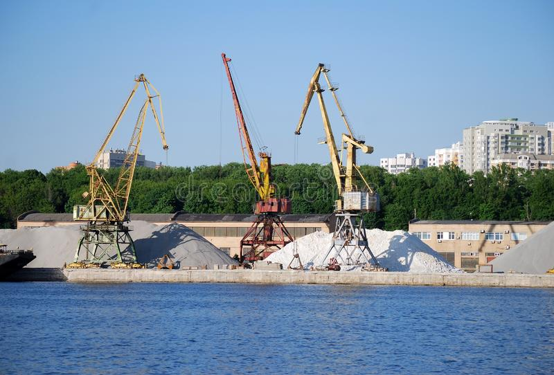 Guindaste industrial para suportes de carregamento das barcas no fundo de pilhas enormes da areia e do cascalho nos bancos do res imagens de stock royalty free