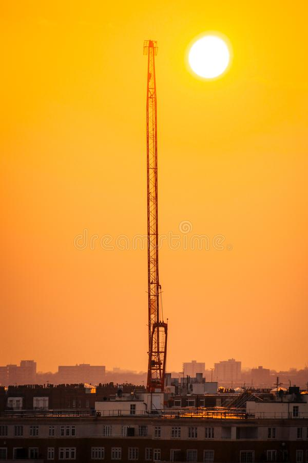 Guindaste vermelho quase vertical com o sol grande no fundo imagens de stock