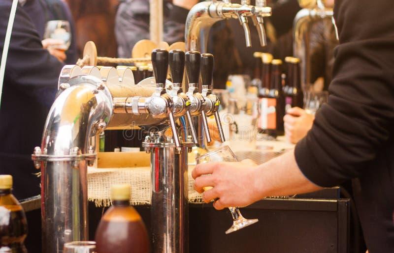 Guindastes da cerveja e povos borrados no festival do alimento da rua imagem de stock