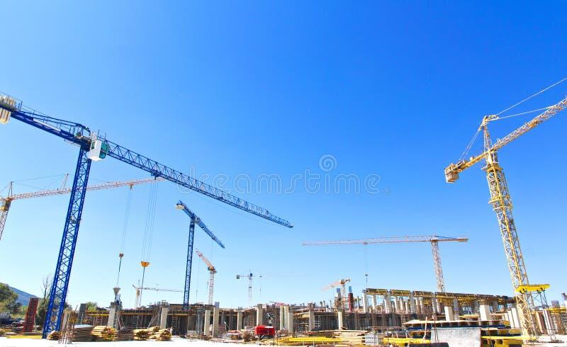 Guindastes de construção em um terreno de construção imagem de stock