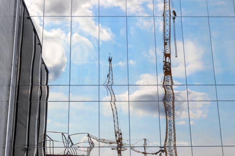Guindastes de construção que refletem em uma construção moderna imagens de stock royalty free