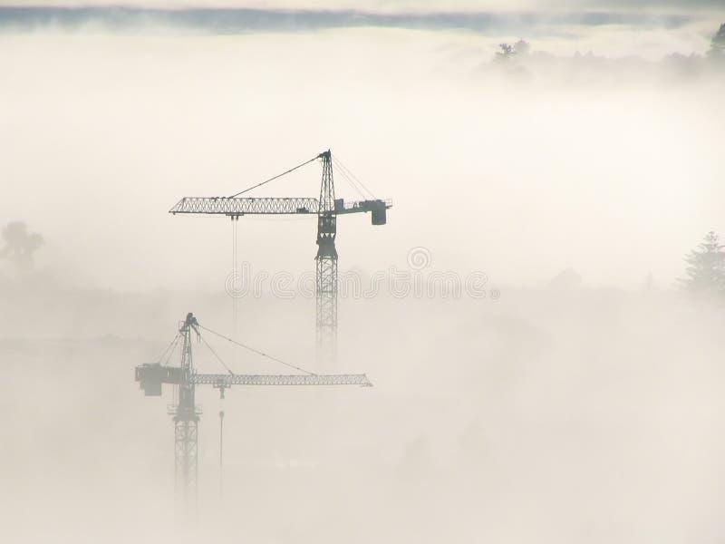Guindastes de torre através da névoa foto de stock