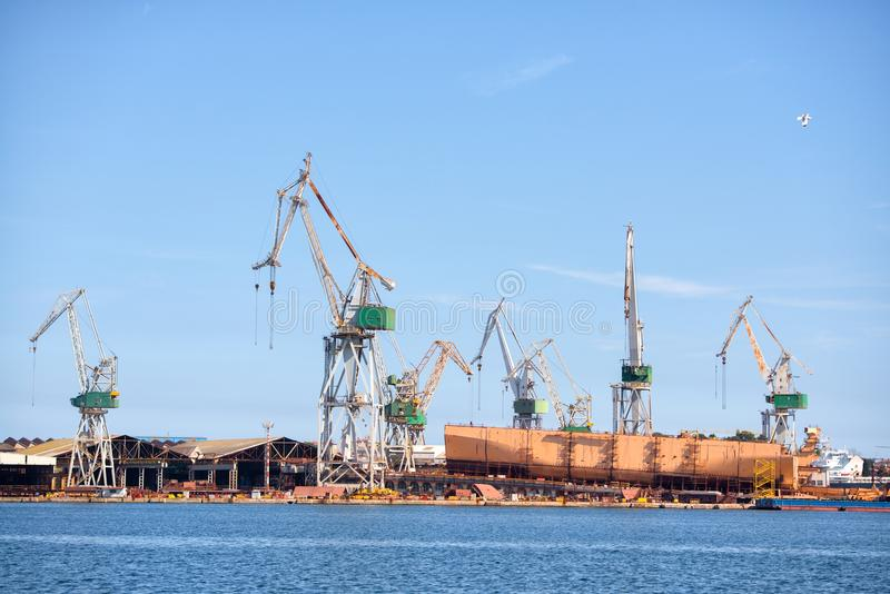Guindastes industriais da carga na doca fotografia de stock royalty free