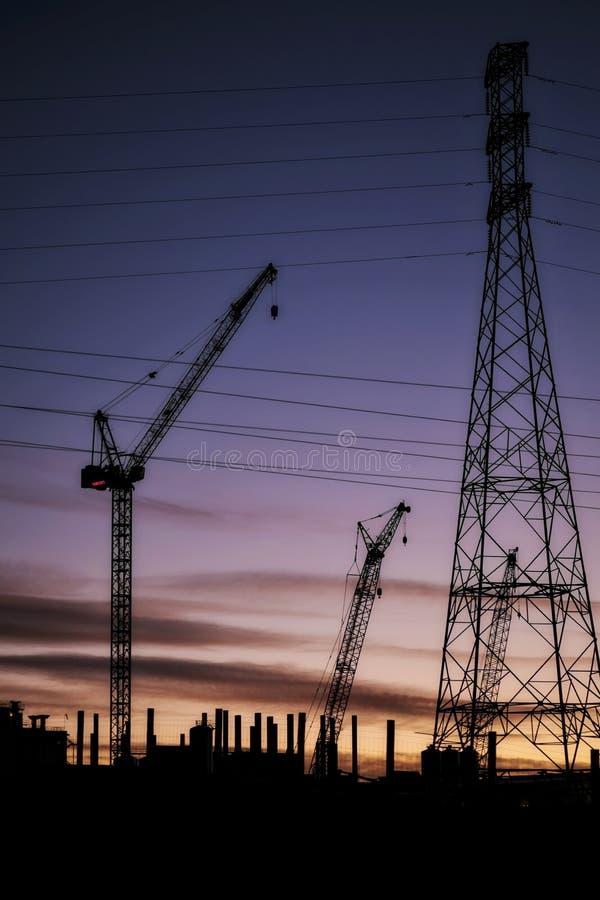 Guindastes, linhas elétricas e fábricas industriais mostrados em silhueta contra o por do sol fotos de stock