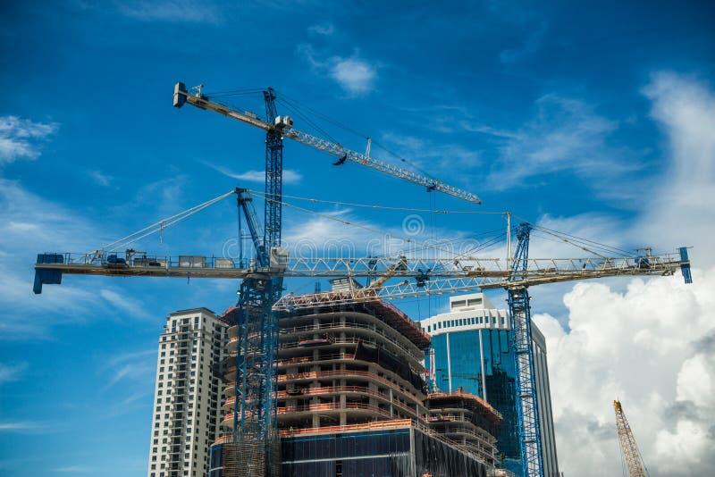 Guindastes na construção moderna do arranha-céus na cidade no dia ensolarado com céu azul imagem de stock