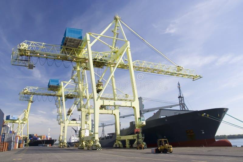 Guindastes portuários que descarregam um navio fotografia de stock royalty free