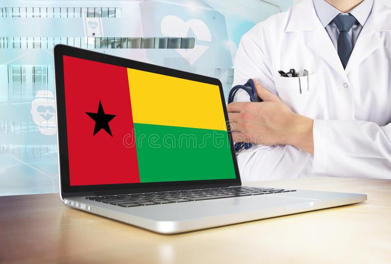 Guinea Bissau healthcare system in tech theme. Flag on computer screen. Doctor standing with stethoscope in hospital. Cryptocurrency and Blockchain concept royalty free stock photos