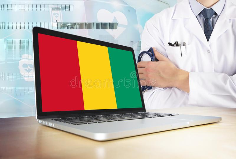 Guinea healthcare system in tech theme. Guinean flag on computer screen. Doctor standing with stethoscope in hospital. Cryptocurrency and Blockchain concept stock photography