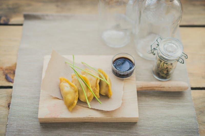 Guiozas japoneses com molho de soja na tabela de desbastamento de madeira imagem de stock royalty free