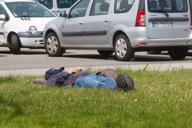 GUIPAVAS, FRANCIA – 1° GIUGNO: uomo che dorme sull'erba, il 1° giugno 2019 fotografie stock