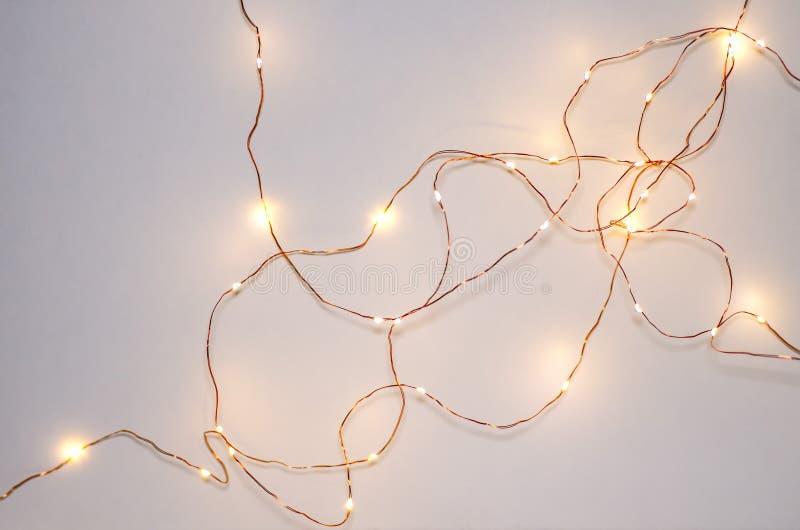 Guirlande électrique rougeoyante sur un fond blanc Lumières de guirlande sur le mur photographie stock