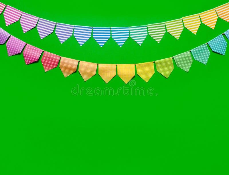 Guirlande colorée de drapeaux Fond vert images stock