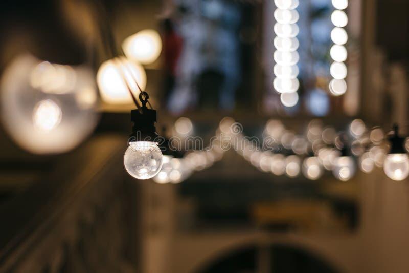Guirlande d'ampoules décor extérieur de café rangées de plan rapproché de perspective de lampes avec le bokeh photo stock