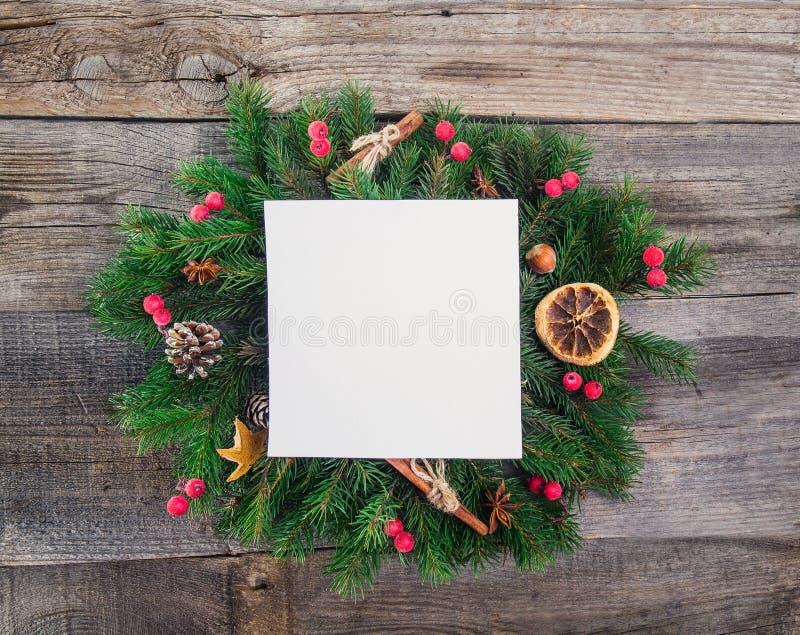 Guirlande de Noël avec les décorations naturelles - baies, cônes, oranges glacées, cannelle, anis avec la carte de papier vide ca image stock