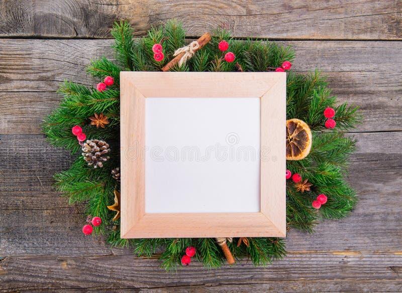 Guirlande de Noël avec les décorations naturelles - les baies, cônes, oranges glacées, la cannelle, anis avec la place ont encadr photos stock