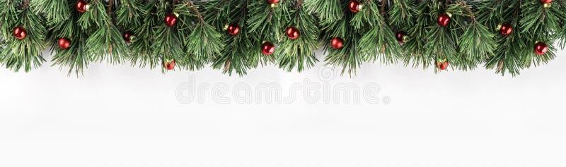 Guirlande de Noël des branches de sapin avec la décoration rouge sur le fond blanc Thème de Noël et de bonne année images libres de droits