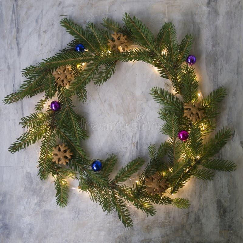 Guirlande de Noël faite de branches de sapin, biscuits, boules colorées et lumières rougeoyantes sur le fond gris Fond d'an neuf photographie stock