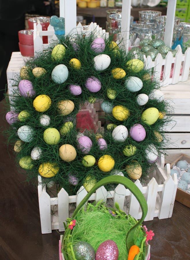 Guirlande de Pâques avec les oeufs colorés dans une boîte de clôture entourée par d'autres décorations et oeufs de Pâques image libre de droits