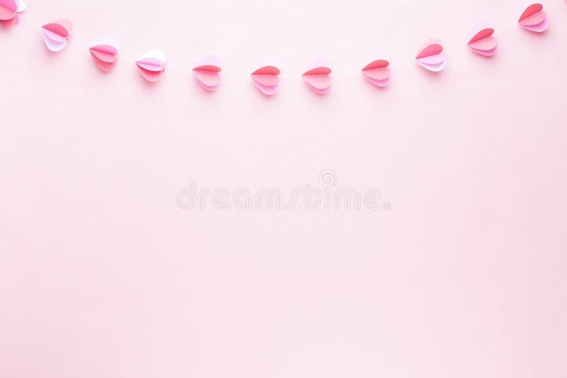 Guirlande de papier colorée des coeurs sur le fond de corail vivant Cartes de voeux de Valentine Day image stock