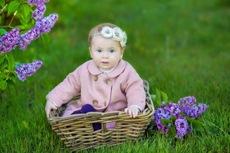 Guirlande de port an de sourire de fleur du bébé 1-2, tenant le bouquet du lilas dehors regarder l'appareil-photo printemps d'été photo stock